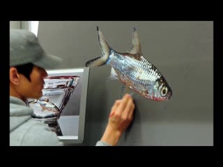 Artist makes realistic painting of fish in a glass