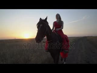 Stock-footage-young-girl-horseback-rider-in-red-dress-riding-horse-on-country-road-in-the-evening-female-rider