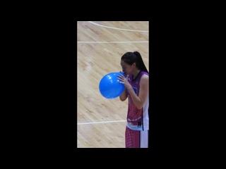 Tall asian basketball girl blows to pop balloon
