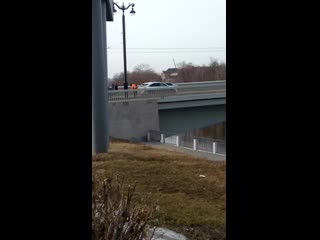 В Омске дворник выкидывает мусор с Юбилейного моста в реку